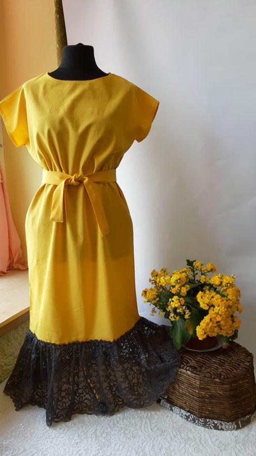 Dzeltena lina kleita ar tumši pelēku mežģīni.